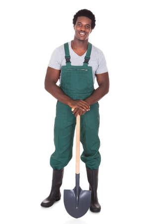 Happy Male Gardener Holding Shovel Over White Background photo