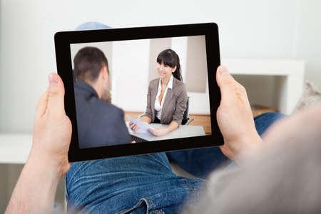 Portr�t eines Mannes bei einem Film auf Tablet drinnen