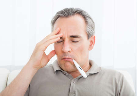 Portrait of a sick man with thermometer in his mouth Stock Photo - 21864296