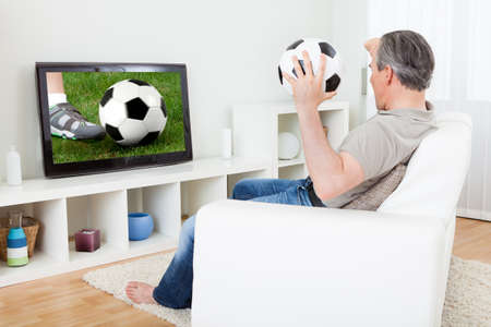 supporter: Portrait of a mature man watching football on television