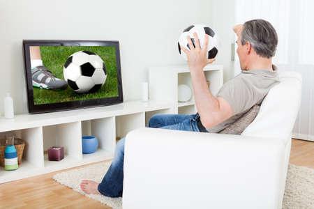 personas mirando: Retrato de un hombre maduro mirando fútbol en la televisión Foto de archivo