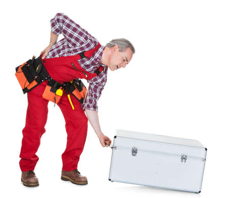 Man Technician With Back Pain Lifting Metal Box isolated on white background photo