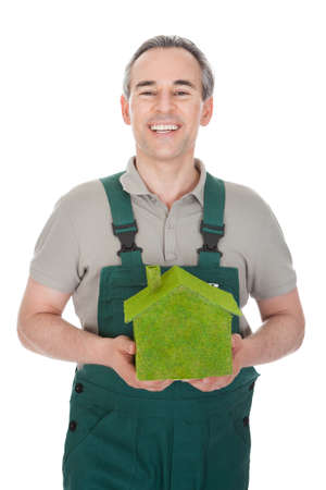 Happy man holding house covered with grass isolated on white background photo