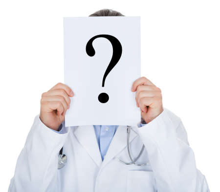 Portrait of doctor holding paper with question mark isolated on white background photo