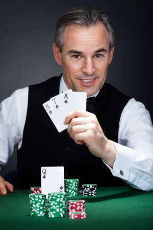 croupier: Close-up of a croupier holding aces of spade and heart