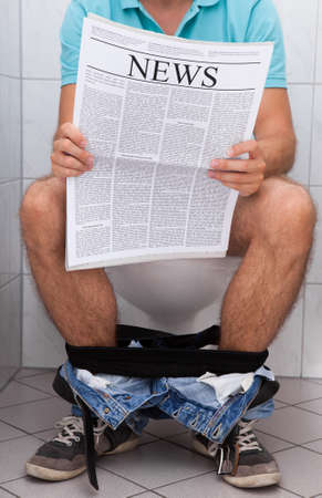 constipation: Close-up of a man in toilet reading newspaper indoors Stock Photo