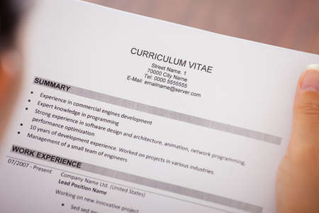 Close-up Of Young Businesswoman Reading Curriculum Vitae At Desk photo