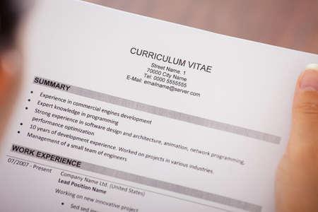 curriculum: Close-up Of Young Businesswoman Reading Curriculum Vitae At Desk