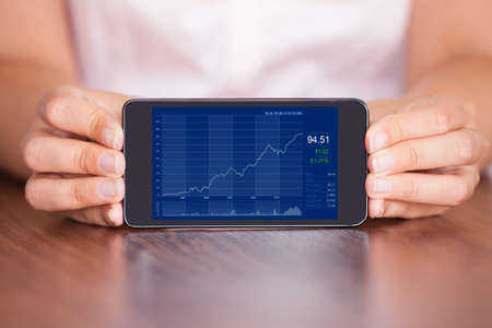 online trading: Close-up Of Young Businesswoman Presenting Graph On Mobile Phone