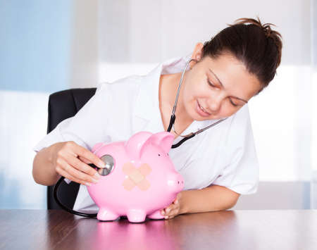 Female Doctor Holding Stethoscope To Pink Piggy Bank Stock Photo - 22000525