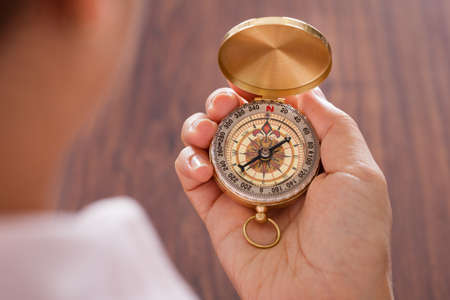business: Close-up Of Female Hand Holding Compass In Hand