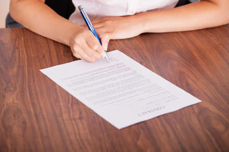 Close-up Of Female Hand Signing Contract Paper photo