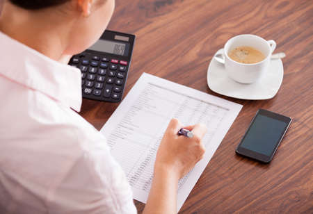 taxes budgeting: Young Businesswoman Working With Calculator And Paper Stock Photo