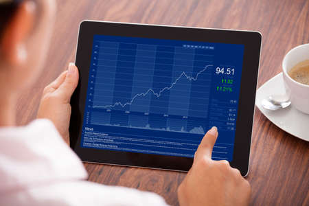 digital stock: Close-up Of Young Businesswoman Looking At Graph On Digital Tablet Stock Photo
