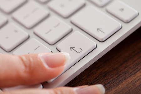 tecla enter: Primer plano de los dedos Mujer presionar la tecla Enter en el teclado