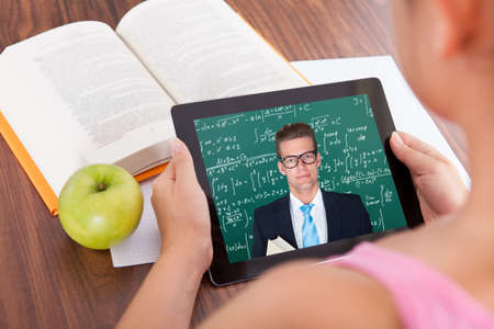 digital learning: Female student watching education tutorials on digital tablet Stock Photo