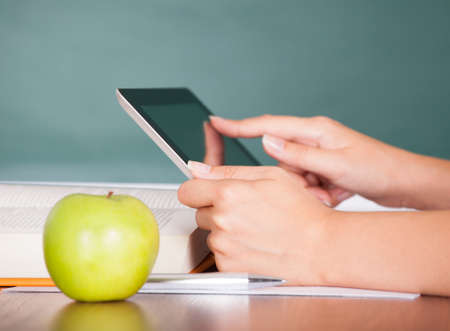 adult classroom: Student using digital tablet beside green apple while studying
