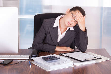 stressed business woman: Young Businesswoman Suffering From Headache At Office