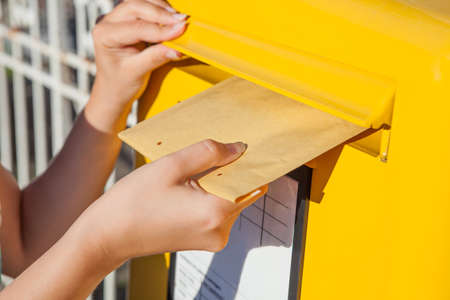 send mail: Close-up of womans hand inserting envelope in mailbox