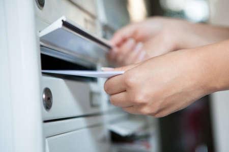 facteur: Gros plan sur la main de femme tenant enveloppe et d'insertion dans la bo�te aux lettres