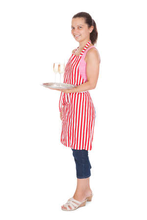 Young Waitress Carrying A Tray With Champagne Glasses on white background photo