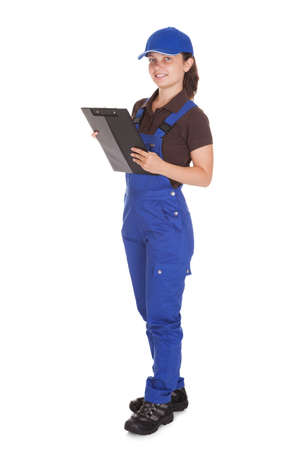 studio happy overall: Happy young female plumber holding clipboard on white background