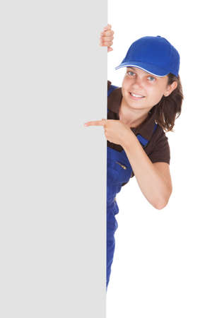 studio happy overall: Smiling female plumber holding blank placard on white background