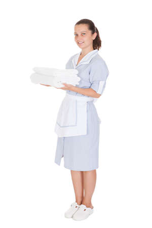 Young Maid Holding Towels Over White Background photo