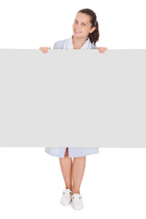 Happy young maid holding blank placard on white background photo
