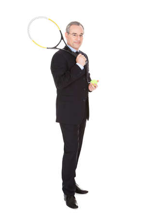Mature Businessman Holding Tennis Racket And Ball Over White Background photo