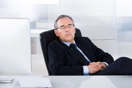 arm chair: Mature Businessman Sleeping With Computer At Desk In Office