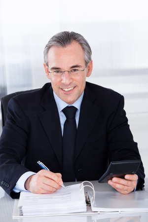 Happy Mature Businessman Calculating Finance With Calculator At Desk photo