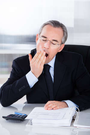 Mature Businessman Yawning While Calculating At Desk photo