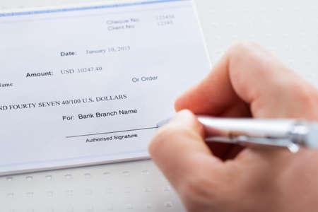 cheque en blanco: Primer plano de mano que sostiene la pluma Preparación verificación de la escritura Foto de archivo