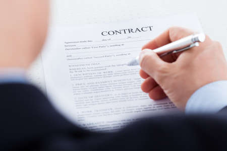 Close-up Of Businessman Hand Holding Pen Over Contract Form photo
