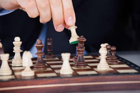 jugando ajedrez: Primer plano de una mano humana jugando al ajedrez