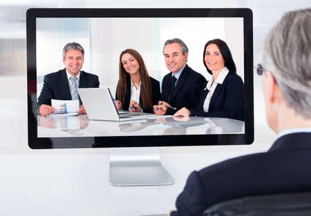 Portré, érett, üzletember részt videokonferencián