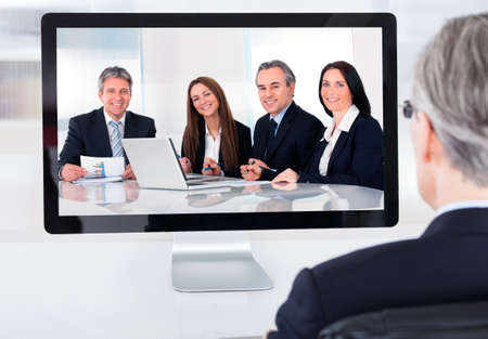 conference room: Portrait of mature businessman attending video conference Stock Photo