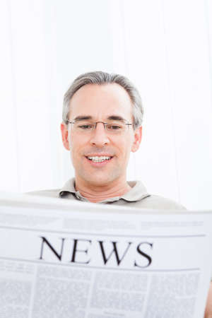Portrait of a happy mature Man Reading Newspaper Stock Photo - 22002659