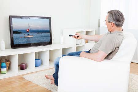 personas mirando: Retrato de un hombre maduro que ve la TV en el país