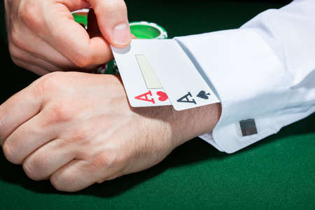 cheat: Close-up of human hand with playing cards in sleeve
