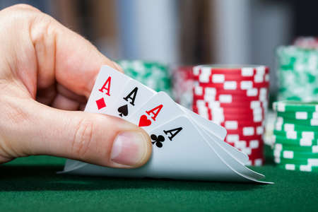 croupier: Close-up of a poker player holding playing cards