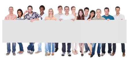 Gruppo di eleganti uomini d'affari professionali piedi in una linea che sostiene un lungo striscione bianco per la vostra pubblicit? o testo