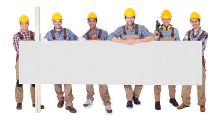 Group Of Happy Workers With Empty Placard Over White Background photo
