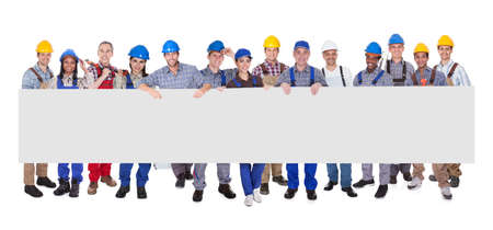 commercial construction: Group of stylish professional business people standing in a line holding up a long blank banner for your advertising or text