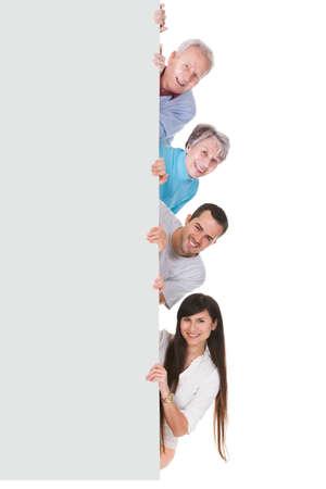 terra arrendada: Grupo de pessoas feliz que mostra o cartaz em branco sobre o fundo branco Imagens