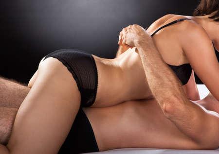 секс: Крупным планом пара занимается сексом, изолированные на цветном фоне Фото со стока