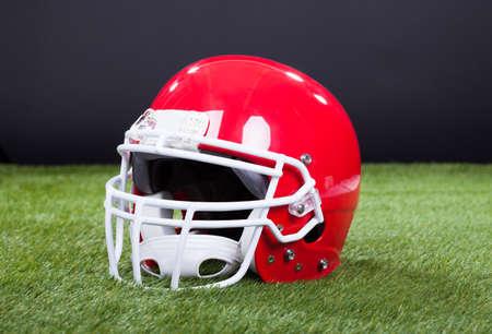 headgear: Red Sports Helmet Lying On Green Grass Field