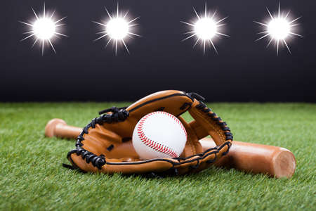baseball ball: Baseball Glove With Baseball And Bat Lying On Green Grass Stock Photo