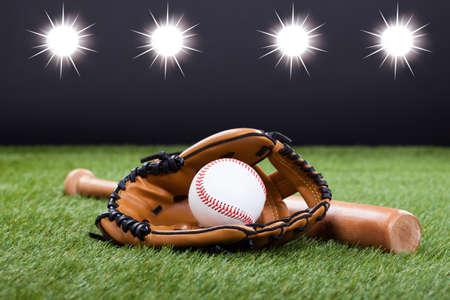 Baseball-Handschuh mit Baseball und Bat auf grünem Gras liegend Standard-Bild
